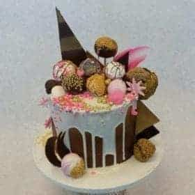 Single Tier Cake with white chocolate drip topped with cake pops, cookies and chocolate pieces