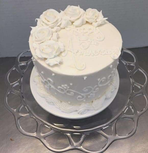Anniversary Cake, An all white cake with buttercream roses on top and scrolls on the side
