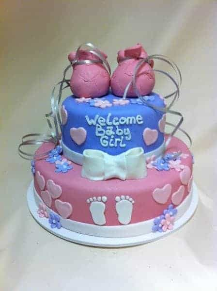 Two tiered Baby Shower Cake, pink colored bottom tier and blue colored top tier with 2 fondant baby booties on top of the cake and a white fondant bow on top of the bottom tier