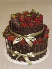2 tier cake with chocolate slabs surrounding each tier and the top of the cake filled with dipped and chocolate drizzled strawberries