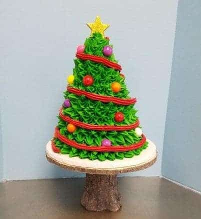 Cake Shaped like a Christmas Tree, with a red buttercream garland and gumball ornaments