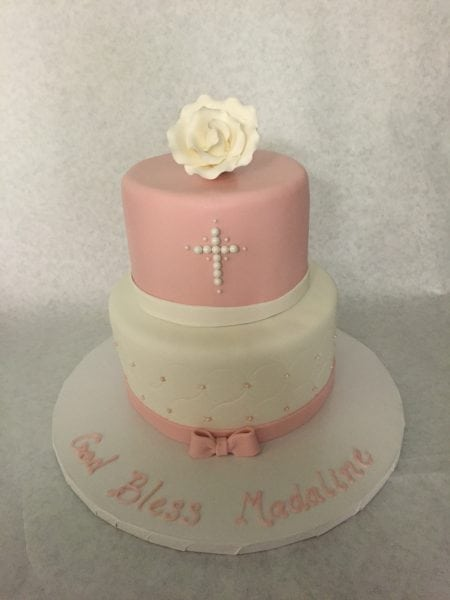 Two tier first communion cake, bottom tier is white with a pink bow and top tier is pink with a white pearl cross all topped with a gumpaste rose