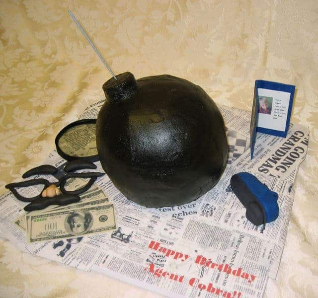 Spy themed birthday cake with shoe phone, disquise, fake ID and magnifying glass in Denver