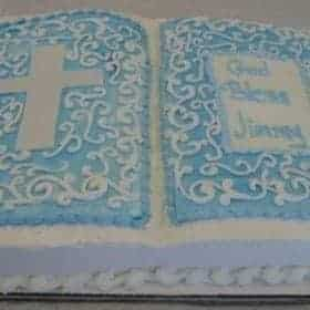 Christening Cake a cake in the shape of an open book with blue pages and script