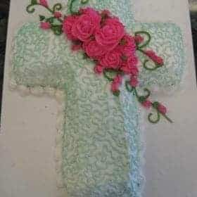 cake shaped like a Cross, with pale blue buttercream lace and deep pink buttercream roses