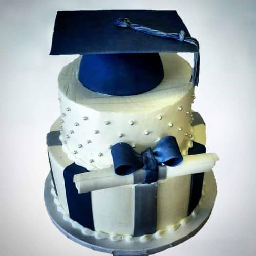 3 tier Graduation Cake, bottom tier with fondant vertical stripes, middle tier with dots and a graduation scroll wrapped in a bow, and the top tier an edible graduation hat
