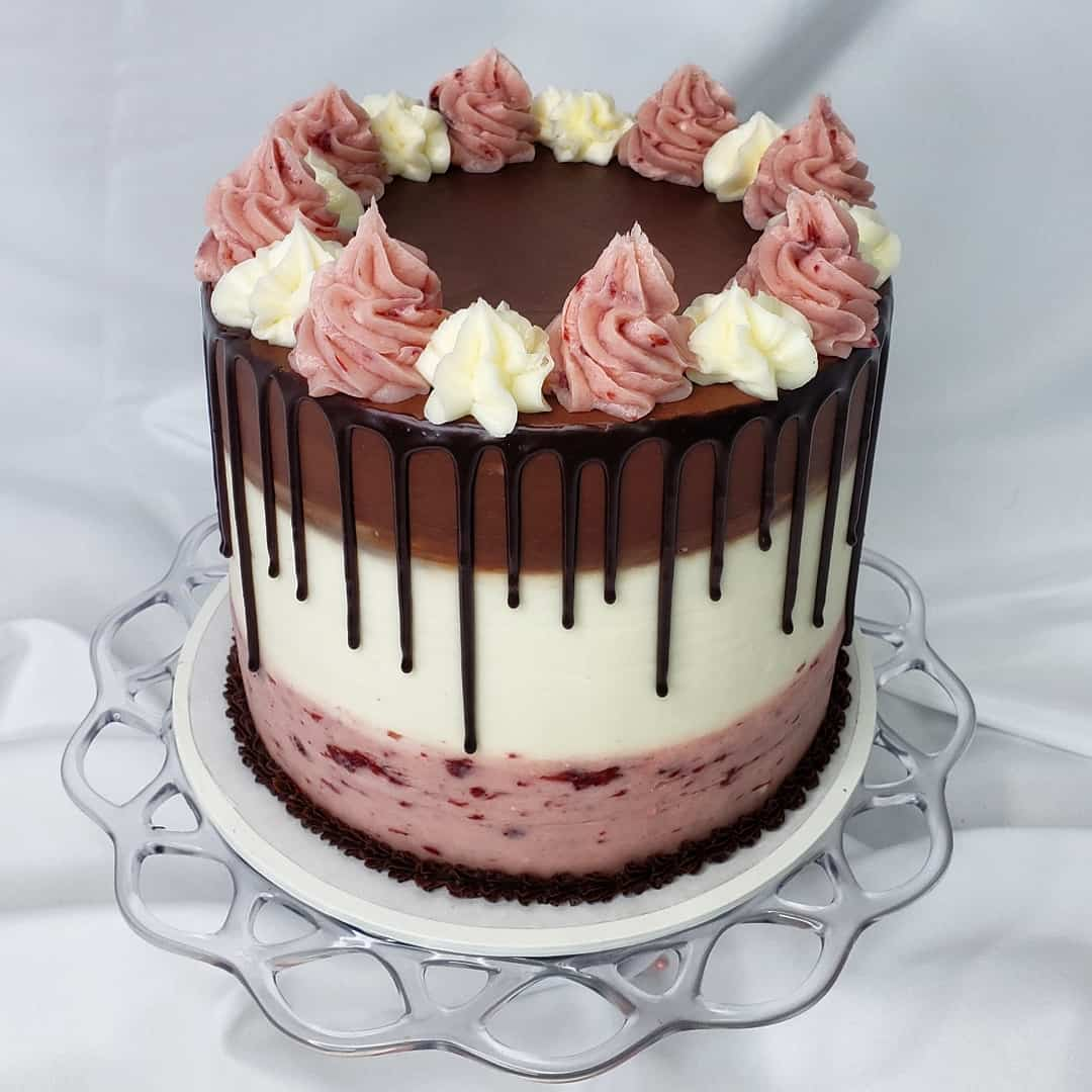 neapolitan cake, with pink Champagne vanilla and chocolate layers, a ganache drip, and buttercream swirls on top