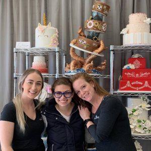 women posing by cake