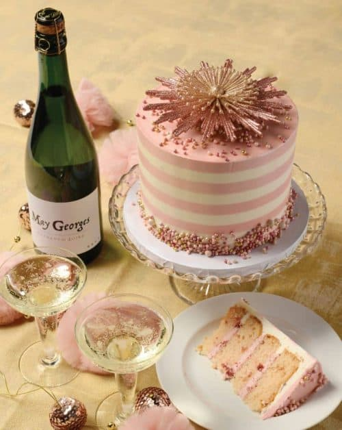 A pink and white striped cake with an ornament on topPhoto by Avid Lyfestyle