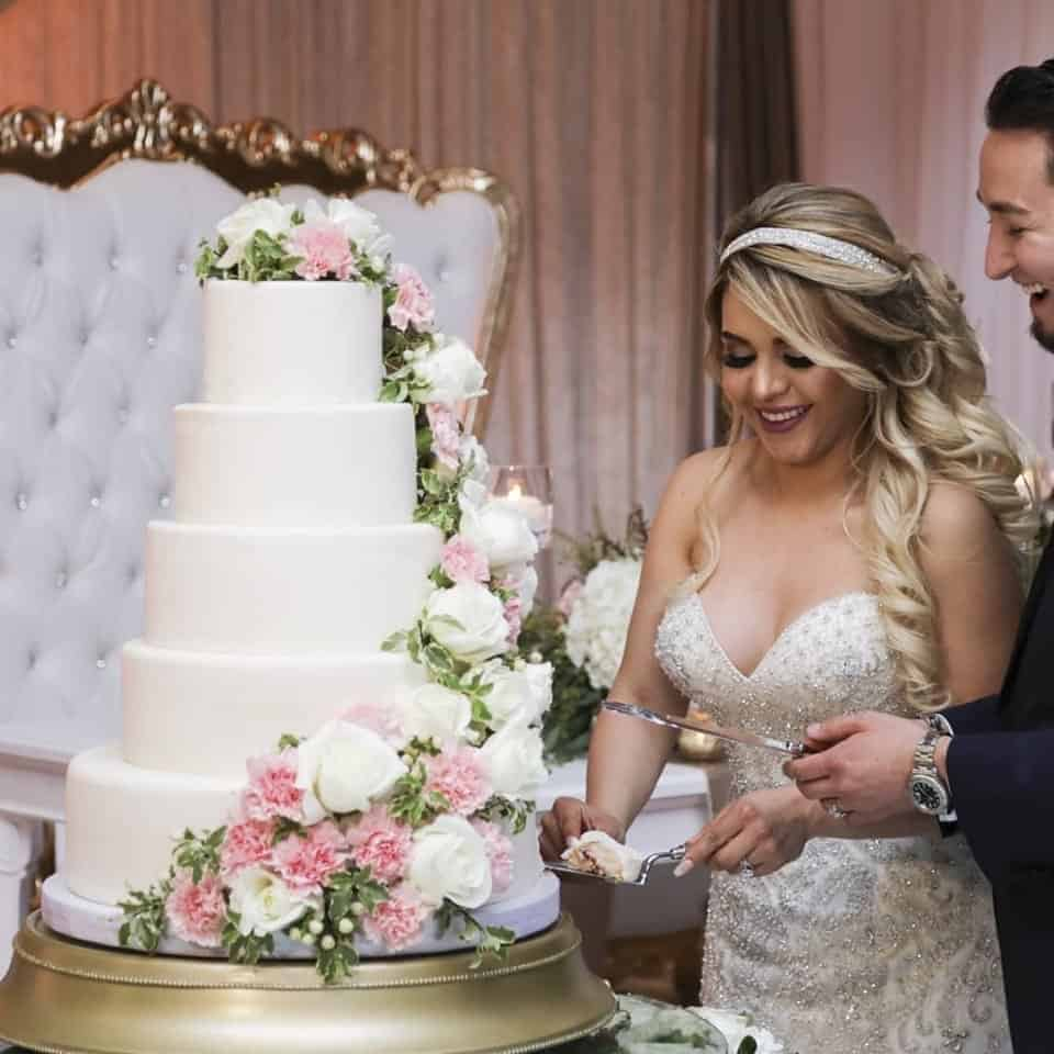 Bride and groom cutting gorgeous wedding cake