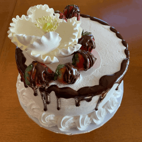 cake with chocolate, flowers, and berries