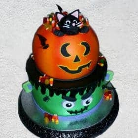 2 tier jackolantern on top of frankenstien cake with black cat on top