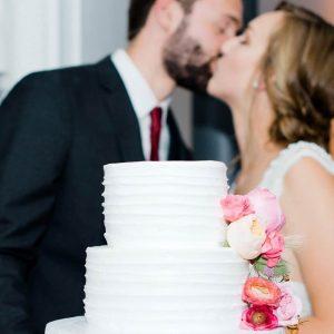 Couple kissing over wedding cake in Denver