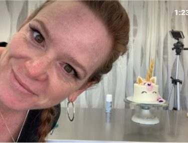 woman looking at camera with cake in background